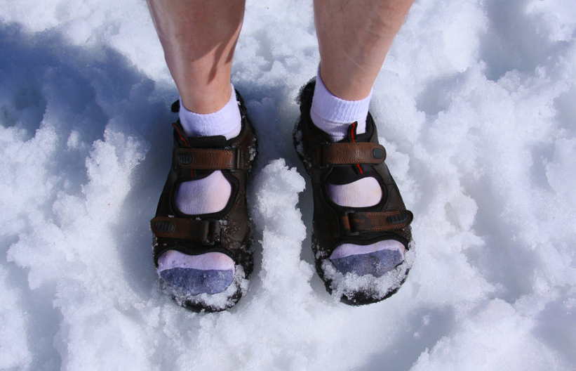 Person on a snow wearing sandals with socks